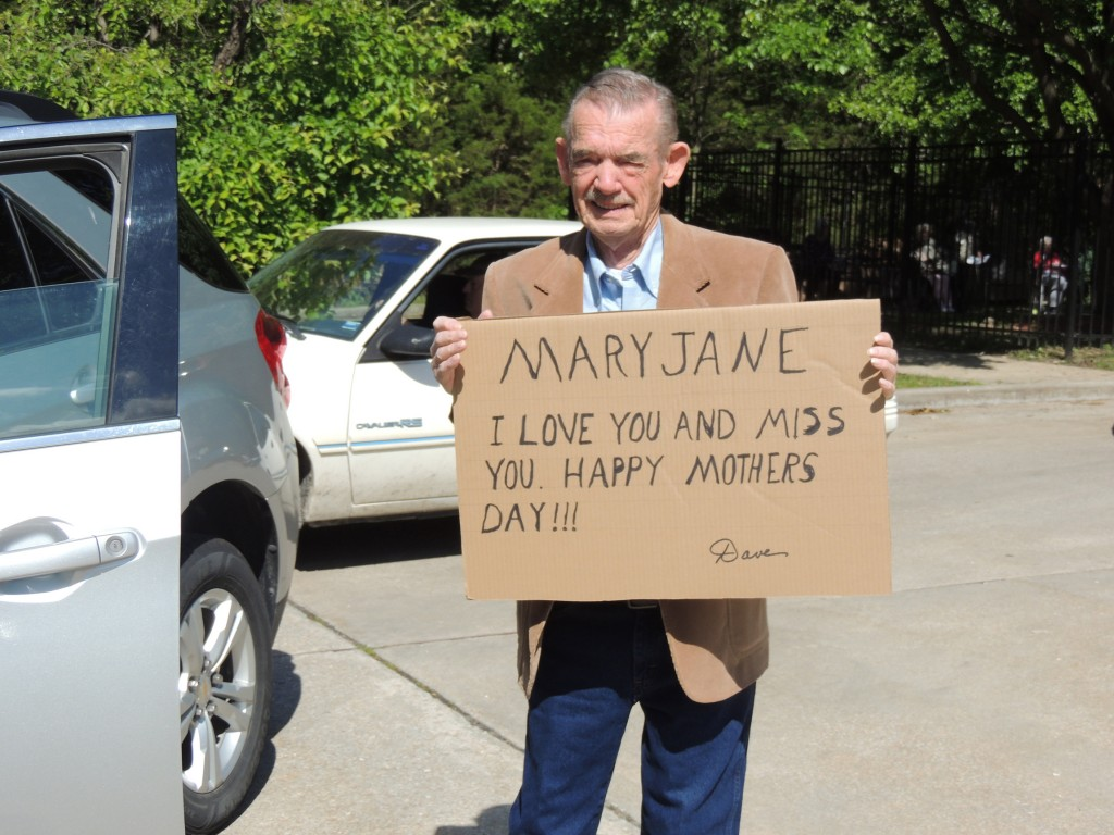 CELEBRATING MOTHER'S DAY amid coronavirus  restrictions, area nursing homes staged parades for their residents. David Cox held a sign for his wife Mary Jane at Warsaw Health & Rehabilitation on Sunday.